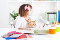 Girl reading a picture book with her cat. Girl and a cat together read a picture book Royalty Free Stock Photo