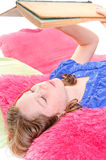 Girl reading on pillows Stock Image