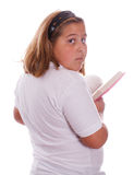 Girl Reading Private Diary. A young girl reading her private diary, isolated against a white background Royalty Free Stock Photo