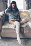 Girl reading and relaxing on a couch stock photography