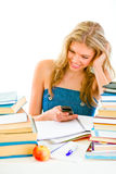 Girl reading sms instead of doing homework Royalty Free Stock Image