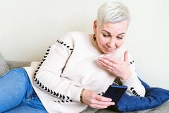 Girl reading an SMS in the smartphone. The emotion of joyful surprise. Women`s short haircut. Fashionable stylish profile with stock images