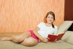 Girl  reading on sofa. Smiling girl with book on beige couch Stock Photo