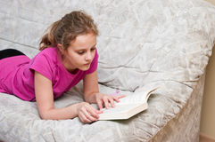 Girl reading on sofa. Young girl lying on a sofa white reading a book Stock Image