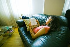 Girl reading on sofa. A view of a young girl reclining on a sofa or couch, reading a book Royalty Free Stock Photo