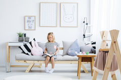 Girl reading on sofa. Cute young girl reading book on stylish sofa in white room Stock Photos