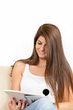 Girl reading on the sofa and smiling. Pretty brunette girl reading on the sofa and smiling Stock Photo