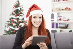 Girl reading something for christmas on the tablet Royalty Free Stock Photography