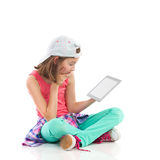 Girl reading something on a digital tablet. Bored girl sitting on the floor with legs crossed and reading something on a digital tablet. Full length studio shot stock photography