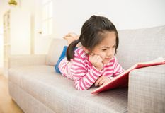 Girl reading story book feel difficult. Happy little asian chinese girl lying down on sofa reading story book feel hard and difficult to understand the content Royalty Free Stock Photo