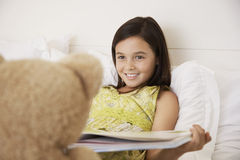 Girl Reading Story Book To Her Teddy Bear Royalty Free Stock Photo