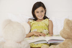 Girl Reading Story Book To Her Teddy Bears. Happy girl reading story book to her teddy bears in bed Royalty Free Stock Photo