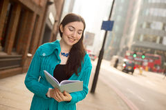 Girl reading in the street Royalty Free Stock Photography