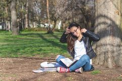 Beautiful young school or college girl with long hair, eyeglasses and black leather jacket sitting on the ground in the park readi stock photography