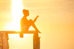 Girl reading at the sunset time stock photo