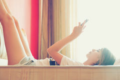 Girl reading tablet on bed Stock Images