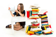 Girl reading on tablet with heaps of unnecessary books stock images