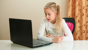 Girl reading text on laptop. Girl sitting on chair and reading text on laptop computer stock video footage