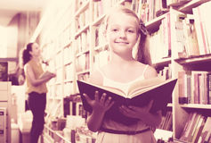 Girl reading textbook in bookstore Stock Image
