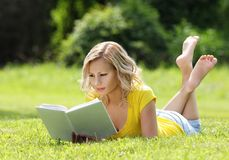 Girl Reading The Book. Blonde Beautiful Young Woman With Book Lying On The Grass. Outdoor. Sunny Day