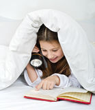 Girl reading under blanket. With flashlight Royalty Free Stock Photos