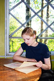 Girl reading by the window. Girl sits at the round table and reads writing book Stock Photos