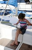 Girl reading on yacht Stock Images
