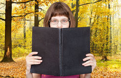 Girl reads big book and autumn woods Stock Photo