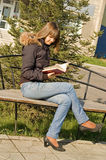 The girl reads the book. Sitting on a shop royalty free stock photography