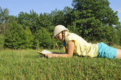 The girl reads the book. The girl in a hat reads a book on a lawn stock images