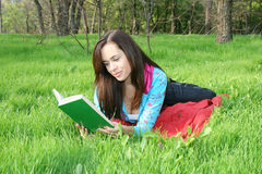 Girl reads the book. The young girl reads the book, laying on a grass Stock Photography