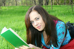 Girl reads the book. The young girl reads the book, laying on a grass Stock Images