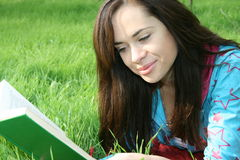 Girl reads the book. The young girl reads the book, laying on a grass Stock Photo