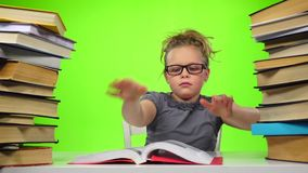 Girl reads the book closes it and takes another. Green screen. Slow motion stock video footage