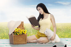 Girl reads book with dog at field Royalty Free Stock Image