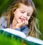 Girl reads book lying on the green grass stock photography