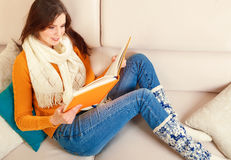 Girl reads a book lying at sofa Royalty Free Stock Photo