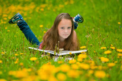 A girl reads a book in the meadow Royalty Free Stock Image