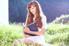 Girl reads a book on the nature Royalty Free Stock Photos