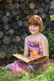 Girl reads the book on the nature Royalty Free Stock Images