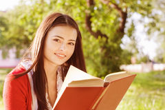 Girl reads book in a park Stock Images