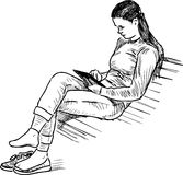 A girl reads a book on a park bench Stock Images