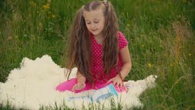 Girl reads a book sitting on the lawn. Little girl reads a book sitting on the lawn stock footage