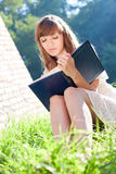 Girl reads a book sitting near the house Stock Images