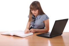 Girl reads the book speckled lays laptop Royalty Free Stock Images