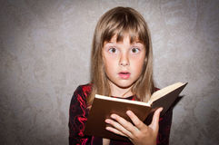 Girl reads book. Teen girl reads book - surprised Royalty Free Stock Image