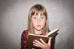Girl reads book. Teen girl reads book - surprised Royalty Free Stock Images
