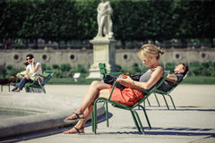 The girl reads the book in the Tuileries garden. Of Paris royalty free stock images
