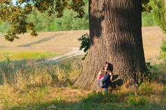 Girl reads the book under the huge oak Royalty Free Stock Photo