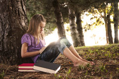 Girl reading books in forest Stock Images